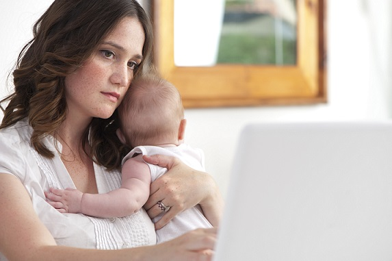 Mother working from home with baby looking stressed